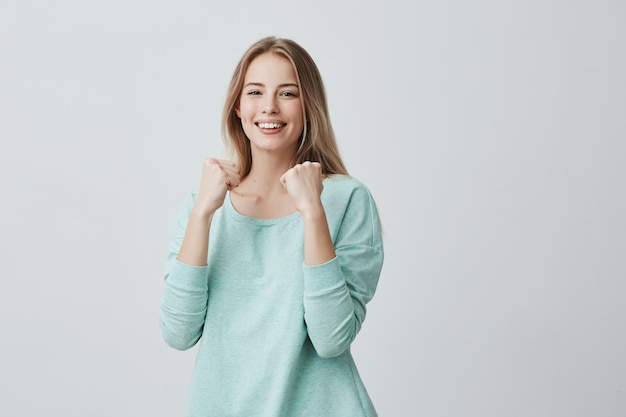 Lucky young female employee rejoicing success at work, smiling broadly, keeping fists clenched. beautiful blonde woman in light blue sweater feeling happy and excited posing Free Photo