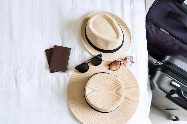 Багаж, соломенная шляпа, солнцезащитные очки и паспорт пары на кровати. приготовьтесь к путешествию, концепция праздника. Premium Фотографии