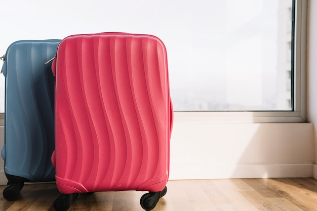 Luggage suitcases near the window on wooden floor Free Photo