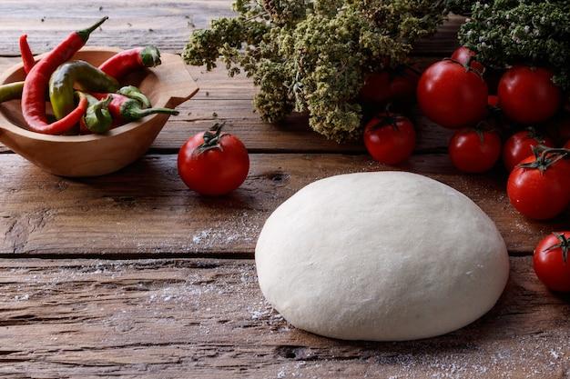 Pezzo di pasta su un tavolo di legno circondato da pomodori e pepe Foto Gratuite