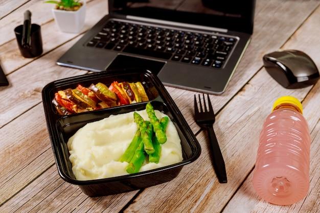 으깬 된 감자, 아스파라거스와 야채 노트북 나무 테이블에 도시락 컨테이너. 프리미엄 사진