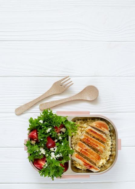 맛있는 건강 식품의 전체 점심 상자 : 복사 공간 흰색 나무 테이블에 샐러드, Coucous 및 구운 치킨 평면도 프리미엄 사진