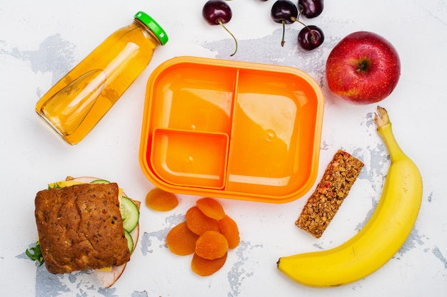 Lunch box, sandwich and fruits Premium Photo