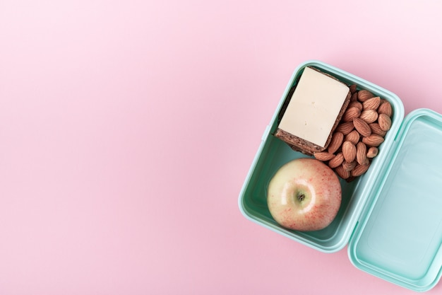 Lunch box with apple, sandwich and almond on pink Premium Photo