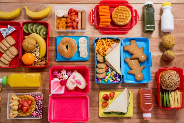 Lunch box with various snack, fruit and sweet food on wooden table Free Photo
