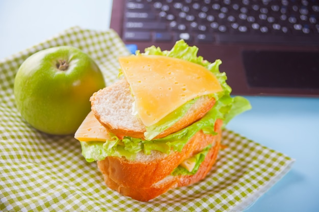 Lunch with sandwich and green apple and laptop on the table. Premium Photo