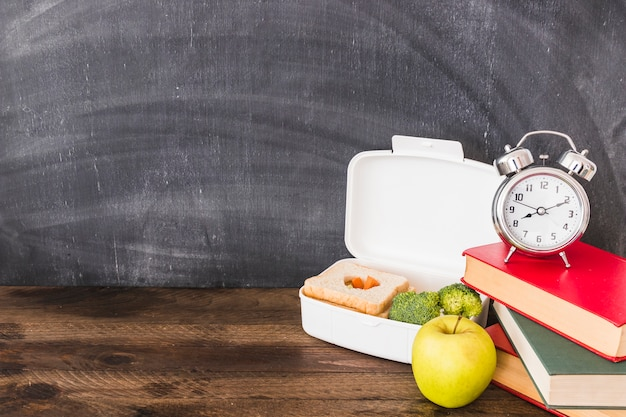 Lunchbox and apple near books and alarm clock Free Photo