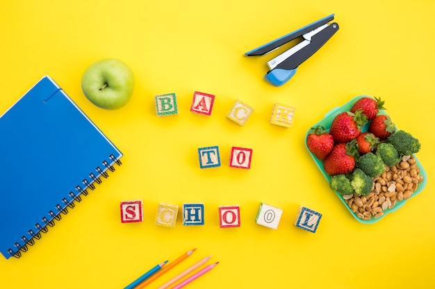 Lunchbox and stationery with writing on table Free Photo