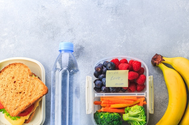Lunchbox with sandwich berries carrots broccoli bottle of water banana on grey Premium Photo