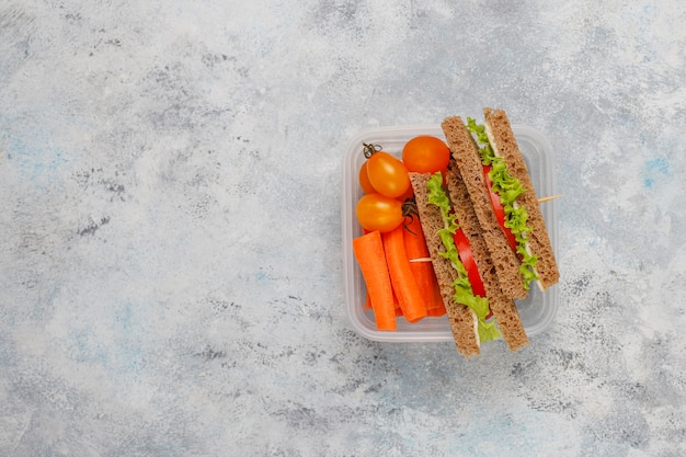 Lunchbox with sandwich, vegetables, fruit on white . Free Photo