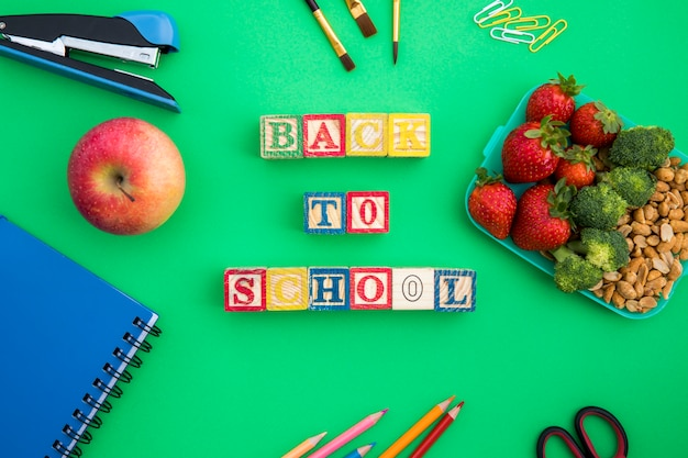 Lunchbox, wooden cubes and stationery on table Free Photo