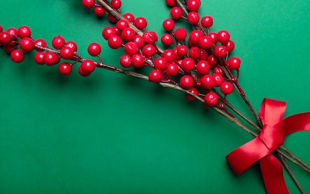 녹색 배경 위에 축제 리본으로 크리스마스 장식으로 붉은 열매 또는 가막살 나무속이 무성한 지점. 프리미엄 사진
