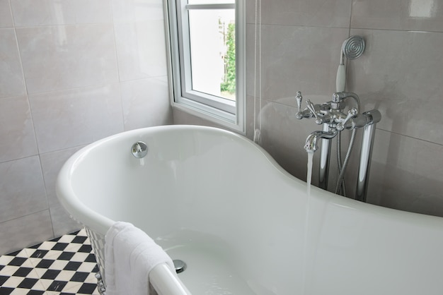Luxurious tub in a modern bathroom, side windows view, bright sunlight, sunny day Premium Photo