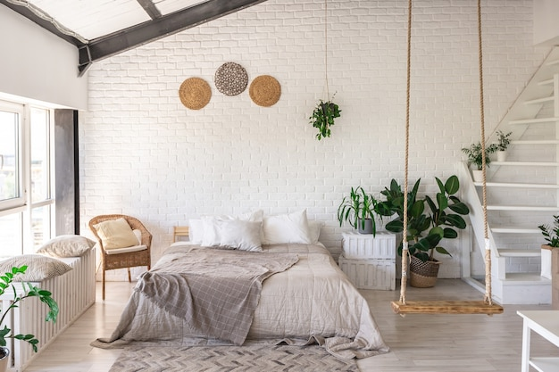 Luxury bedroom design in a rustic cottage in a minimalist style. white walls, panoramic windows, wooden elements of decoration on the ceiling, rope swings in the middle of a spacious room. Premium Photo
