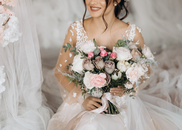 Luxury bride holding a big bouquet of flowers Free Photo