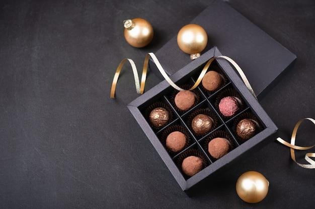 クリスマスデコレーションゴールデンボールと蛇紋岩と黒の背景にブラックボックスで高級チョコレートトリュフ。クリスマスの手作りチョコレートの箱。 Premium写真