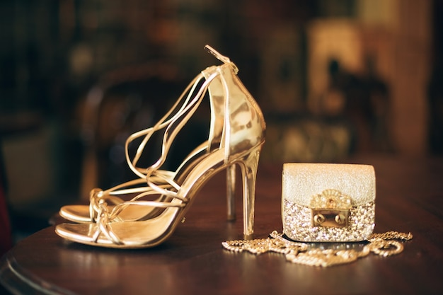 Luxury fashion woman accessories, golden heeled shoes, little evening purse, elegant style, vintage style, sandals footwear Free Photo
