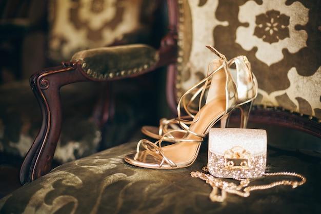 高級ファッションの女性のアクセサリー、金色のかかとの靴、小さな夜の財布、エレガントなスタイル、ヴィンテージスタイル、サンダルの靴 無料写真