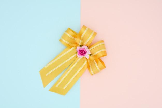 Luxury gold satin ribbon on pink and blue background Premium Photo