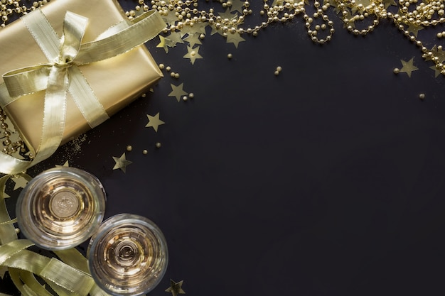 Luxury golden gift box with two glass champagne on shine black background. christmas party. flat lay. view from above. xmas. Premium Photo