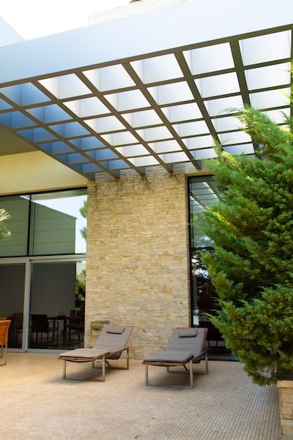 豪華な家、手入れの行き届いた中庭、緑豊かな庭園、庭でリラックスできる居心地の良いサンベッド Premium写真