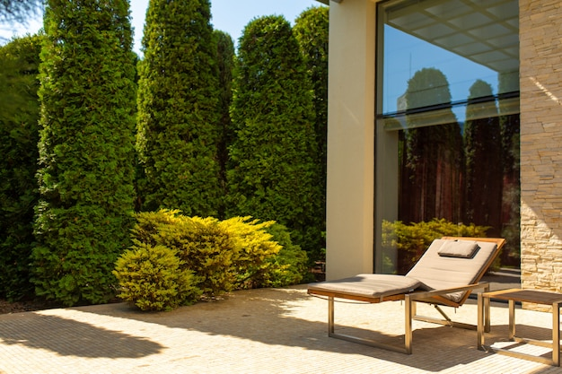 Luxury house, well-kept courtyard with a green garden and cozy sunbeds for relaxing in the garden Premium Photo