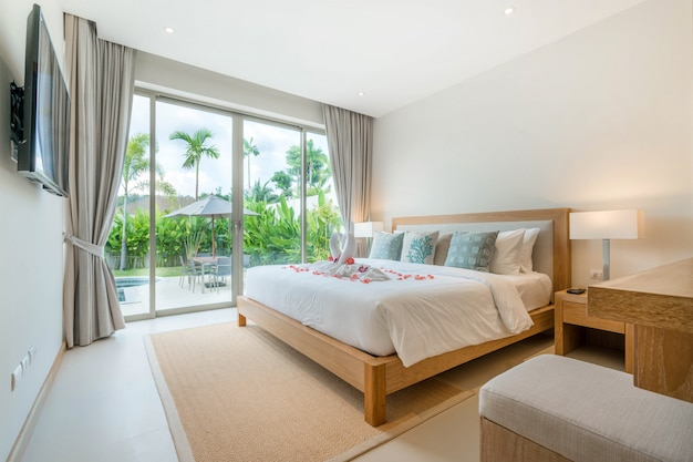 Luxury interior design in bedroom of pool villa with high raised ceiling and roses on bed in the house or home building Premium Photo