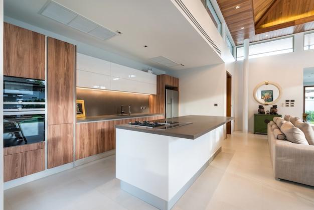 Luxury interior design pool villa in kitchen area which feature island counter, built in f Premium Photo