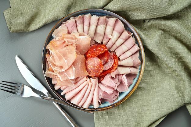 Роскошные итальянские мясные закуски для вина в керамической тарелке на деревянном столе, вид сверху на салями, ветчину, прошутто и чоризо Premium Фотографии
