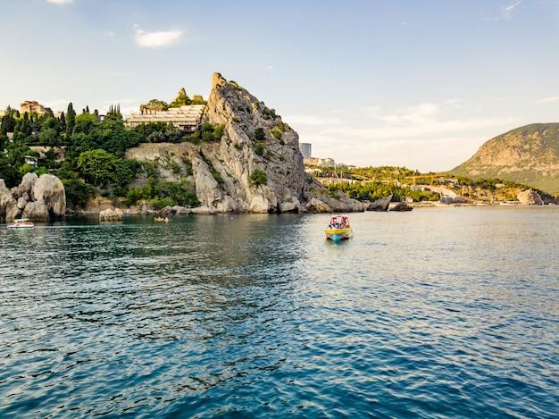 Luxury motor boat near the rock sea coast in europe city bay Premium Photo