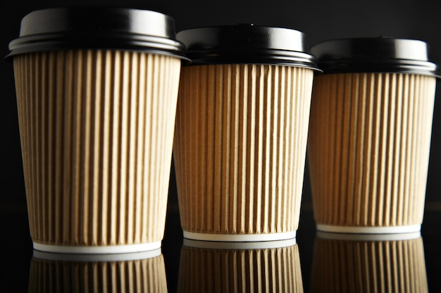 Luxury set of brown take away cardboard paper cups closed with caps isolated on black and mirrored. retail  presentation Free Photo
