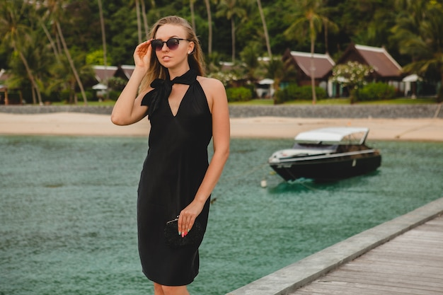Роскошная сексуальная привлекательная женщина, одетая в черное платье, позирует на пирсе в роскошном курортном отеле, в солнцезащитных очках, летние каникулы, тропический пляж Бесплатные Фотографии