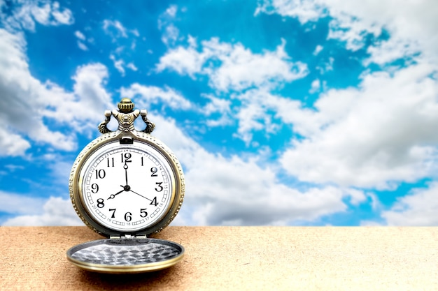 Luxury vintage golden pocket watch on wooden over blue sky, abstract for time concept with copy space Premium Photo
