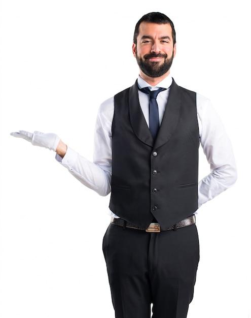 Cameriere di lusso in possesso di qualcosa Foto Gratuite
