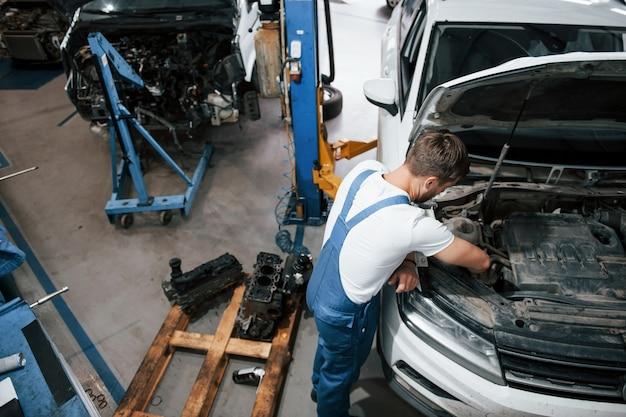 Роскошный белый автомобиль. сотрудник в синей форме работает в автомобильном салоне Бесплатные Фотографии