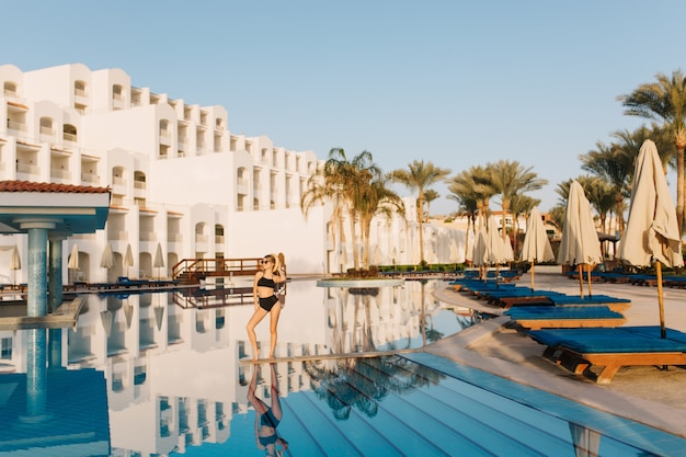 Luxury white hotel egypt, eastern style, resort with nice big pool. pretty girl, model wearing black swimsuit posing in the middle of the pool. vacation, holiday, summertime. Free Photo