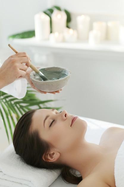 Lying woman receiving a facial beauty treatment. Free Photo