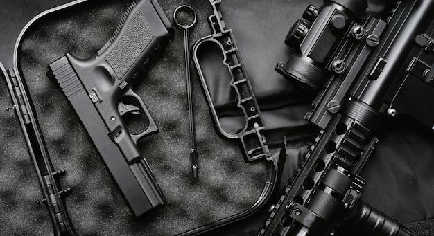 武器、軍隊、アサルトライフル銃(m4a1)、黒の背景に拳銃9 mmの軍事機器。 Premium写真