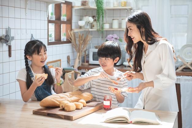 台所で幸せなアジア家族。母と息子と娘と子供たちはパンにイチゴの山mを広げ、自宅で余暇活動をしています。 Premium写真
