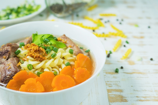 Macaroni soup with pork and carrot on white wooden table Free Photo