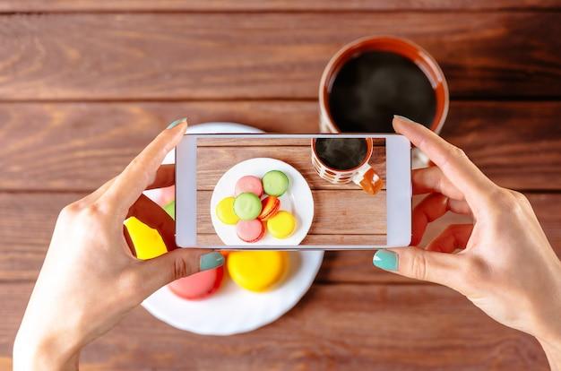 Женщина принимая фото десерта macarons. Premium Фотографии