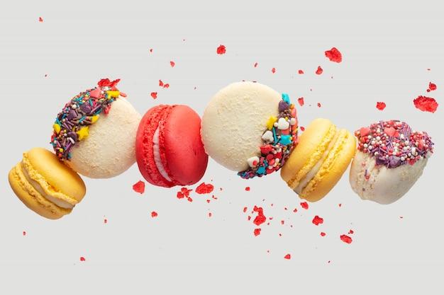 Красочные macarons печенье. французские пирожные. сладкие и красочные французские миндальные печенья падают или летят в движении. с ломтиками Premium Фотографии