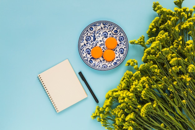 Macaroons on ceramic plate; spiral notepad; pen and bunch of yellow flowers on blue background Free Photo
