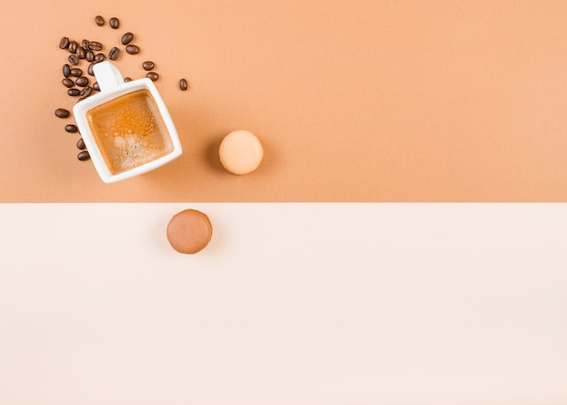 Macaroons; coffee cup; and roasted coffee beans on dual background Free Photo