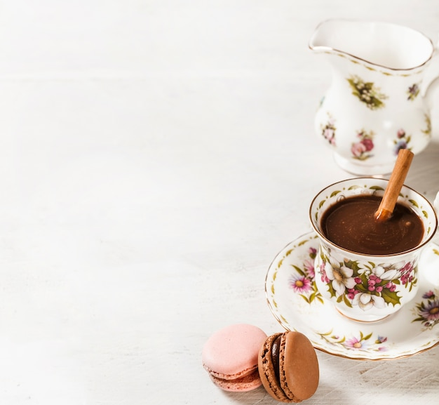 Macaroons and hot chocolate with cinnamon stick in ceramic cup on white textured backdrop Free Photo