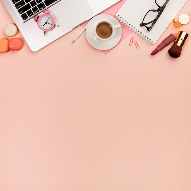 Macaroons,makeup brushes with alarm clock on laptop and stationeries on peach backdrop Free Photo