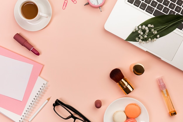 Macaroons,makeup products,spiral notepads,coffee cup and laptop on peach colored backdrop Free Photo