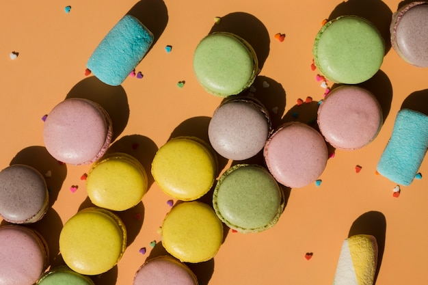 Macaroons and marshmallow with sprinkles on brown background Free Photo