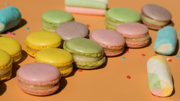 Macaroons and marshmallows on colored backdrop Free Photo