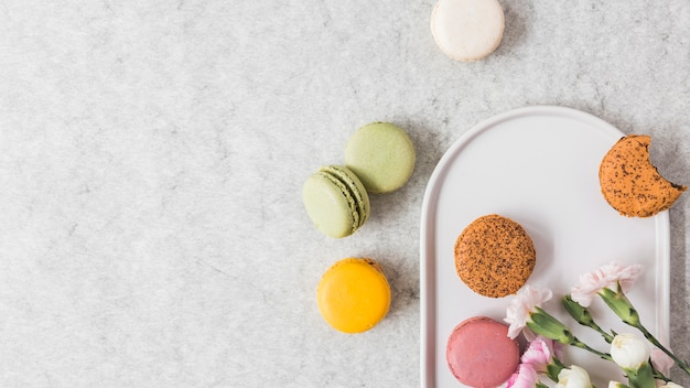 Macaroons on plate over textured background Free Photo